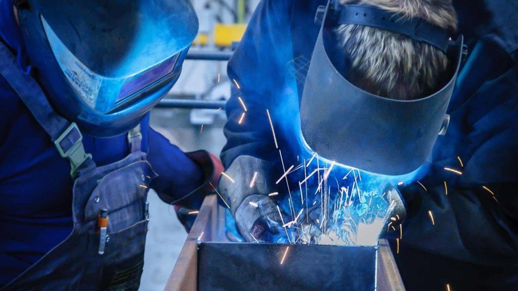 A welding instructor and student practicing welding techniques