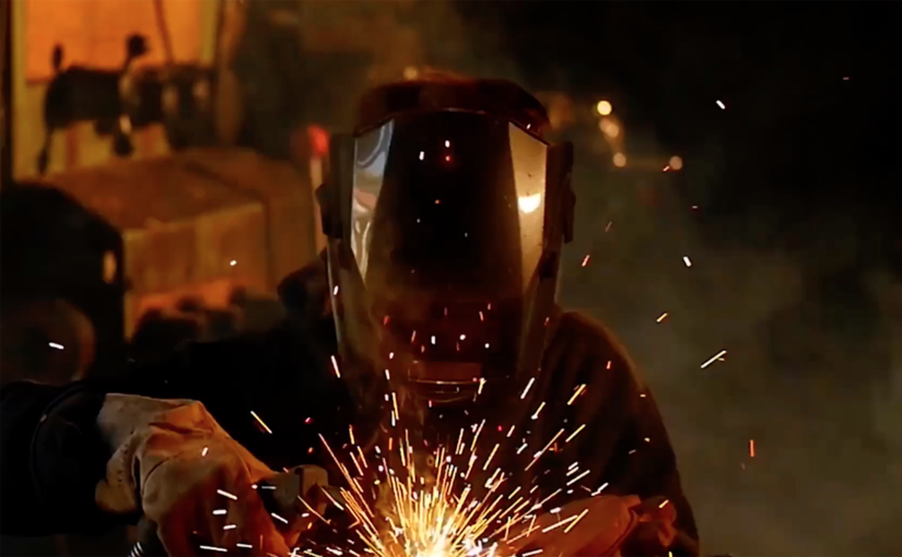 A welder produces sparks in a dark workshop, contributing to the output of a larger welding operation.