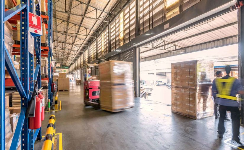 Warehouse workers operate forklifts and move boxes in a busy distribution environment.