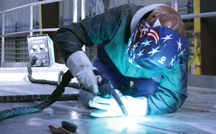 A welding machine operator wearing an American flag helmet welds an aluminum floor on his hands and knees.