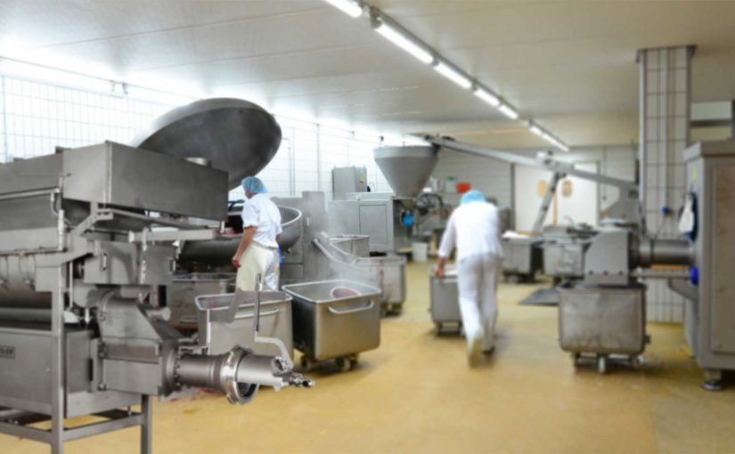 Workers use large-scale mixing machinery—including a mixer with bottom injection nozzles—in a busy food processing facility.