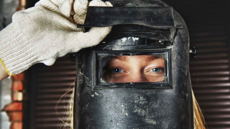 A woman with long blonde hair confidently peers from the open lens of a welding helmet.