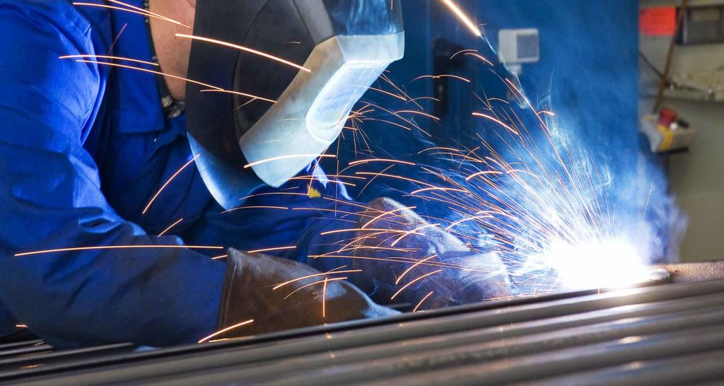 A welding machine operator uses a MIG gun to perform a weld using metal-cored wire.
