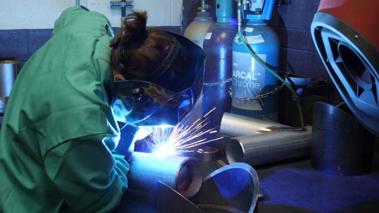 Long-time welder Sue Silverstein cuts a thick metal pipe.