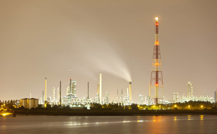 An oil refinery emits a healthy, smoke-free flare on a cloudy evening.